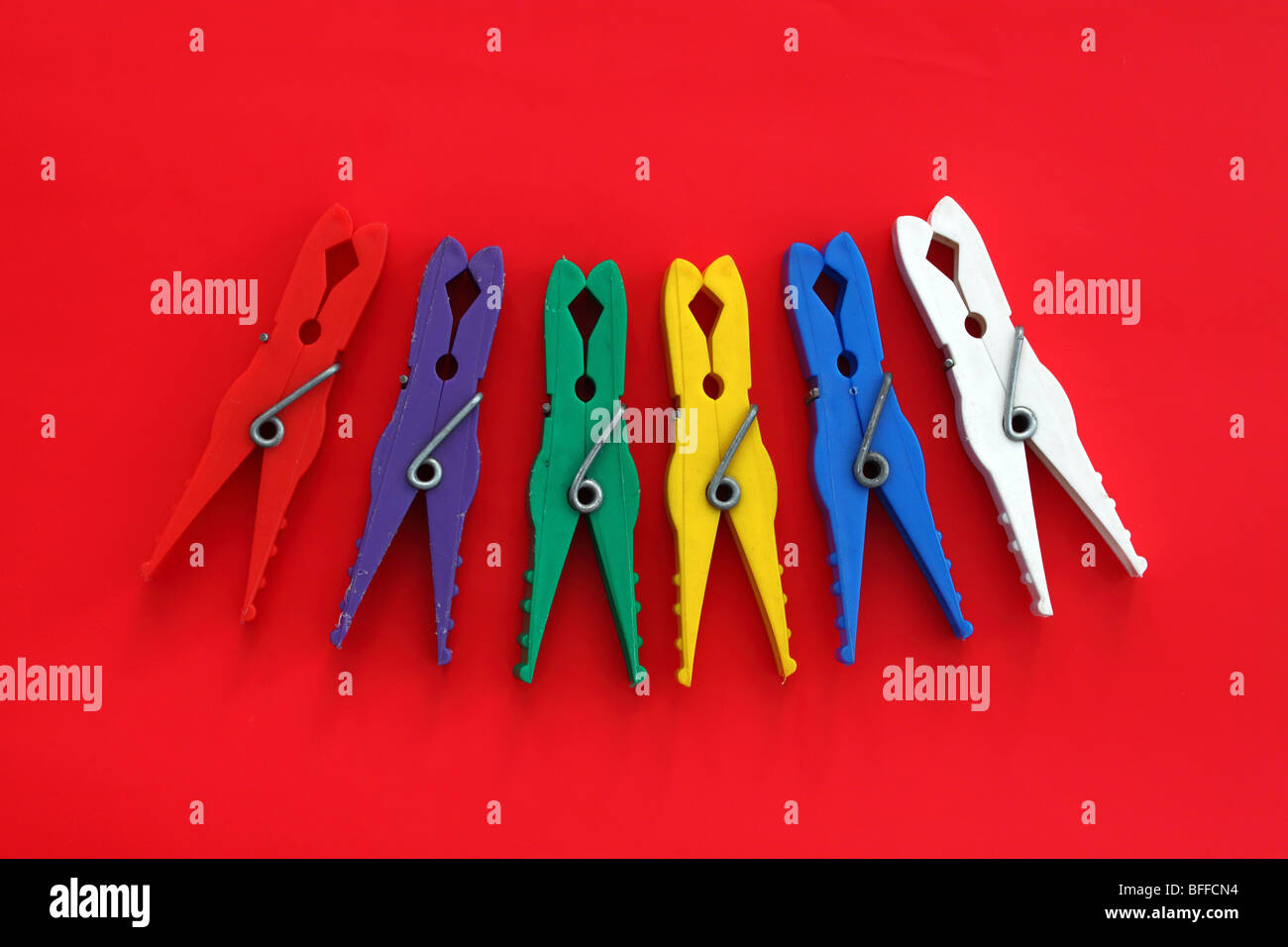 Multicolor laundry clips on red background - Stock Image