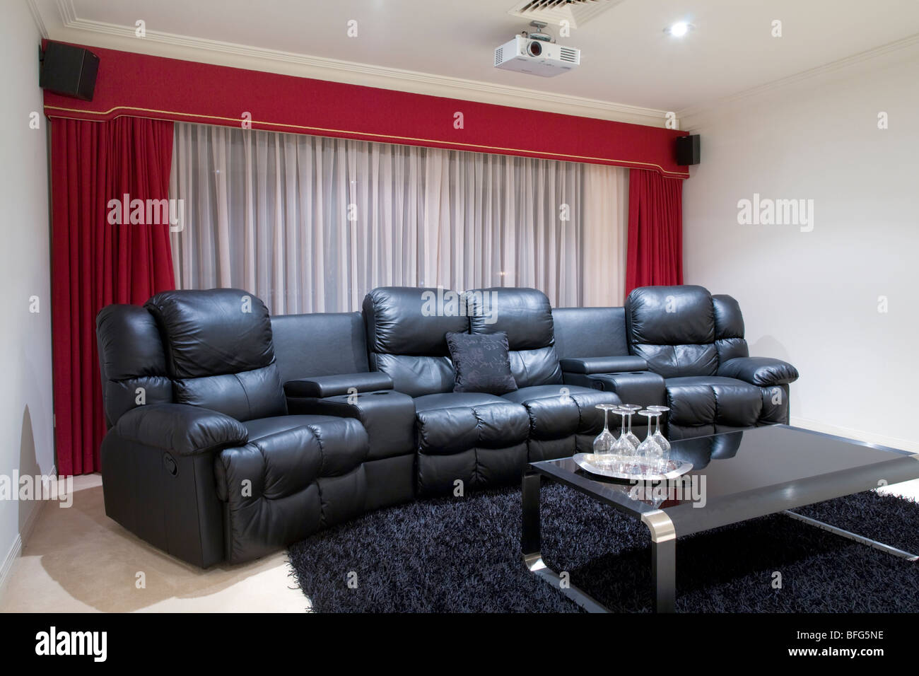 home theater room with black leather recliner chairs red curtains black rug and table with wine glasses & home theater room with black leather recliner chairs red curtains ...