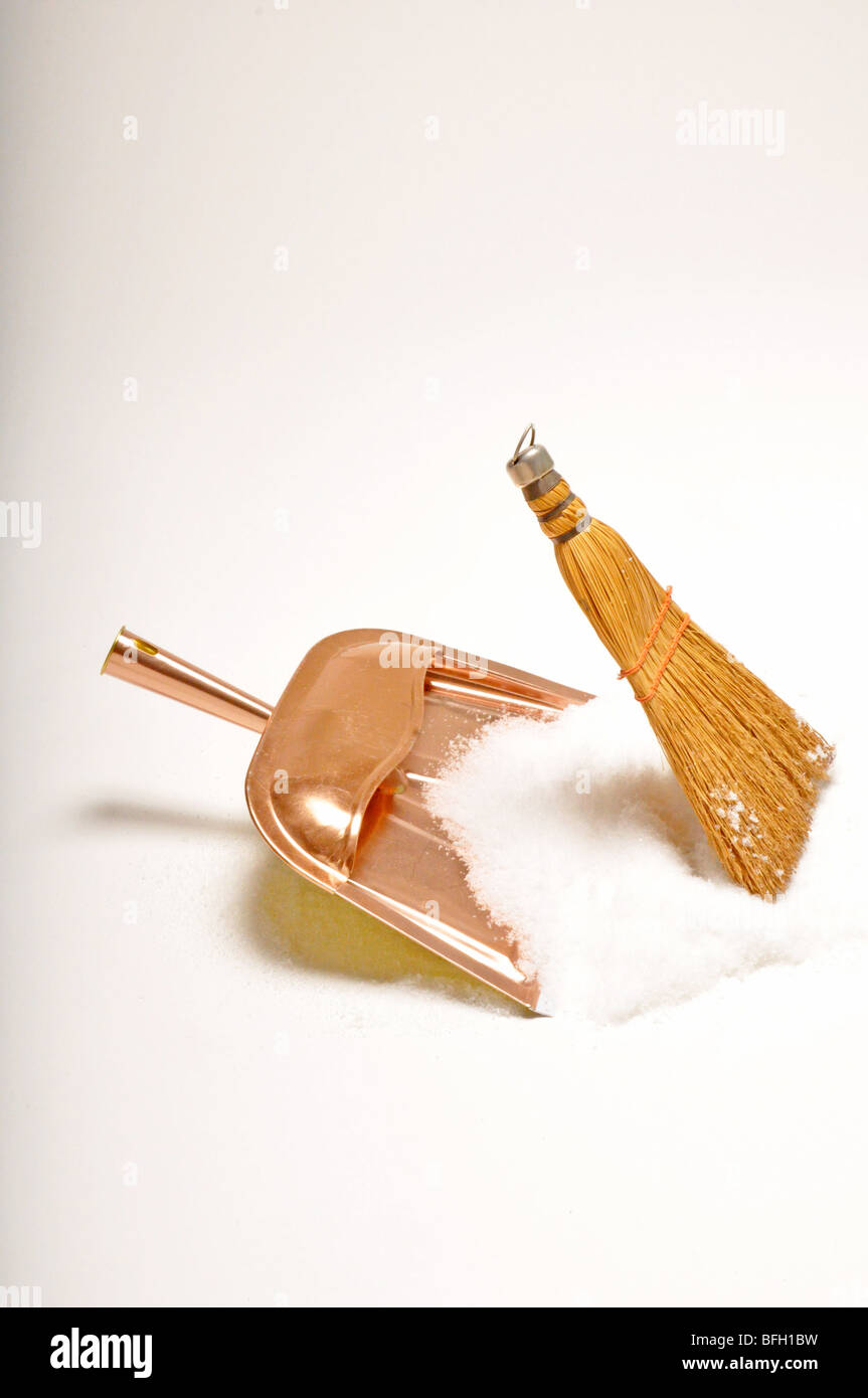 dust pan and broom sweep up white snow, no people. - Stock Image