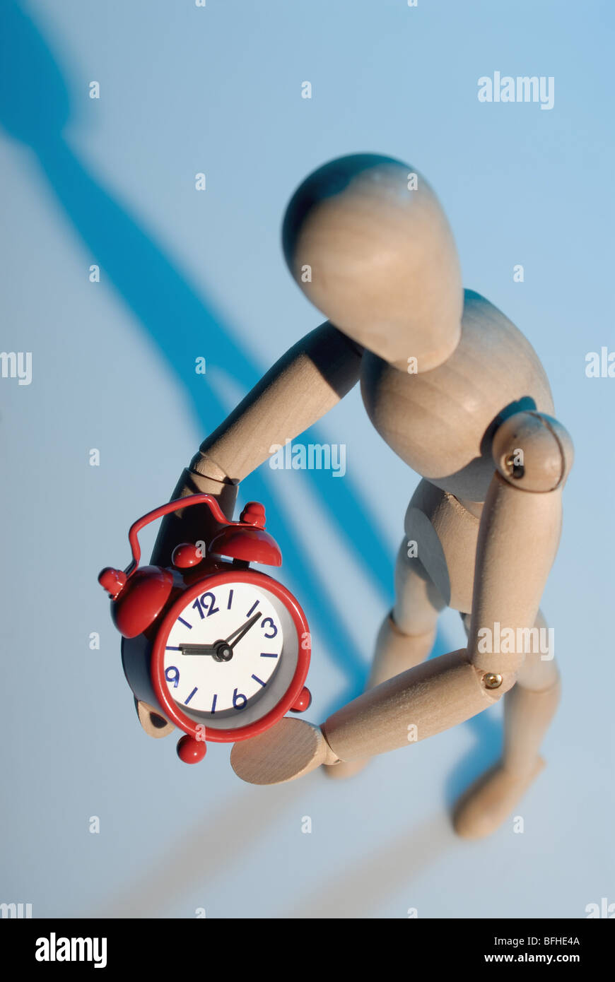 wooden model and red alarm clock,metaphor of stopping the time - Stock Image