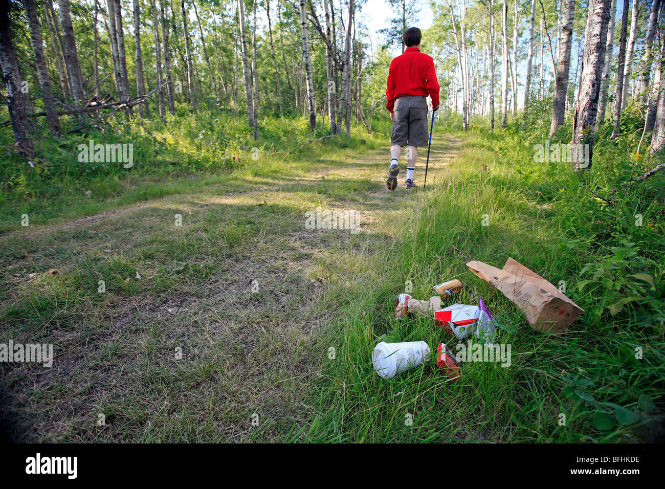 Middle age male hiking on forest trail with garbage on the ground. - Stock Image
