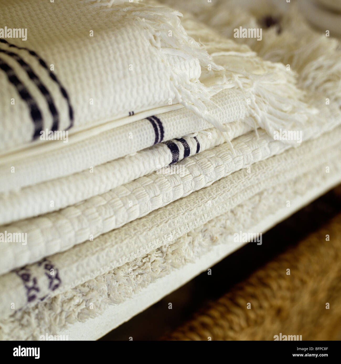 A pile of folded cotton towels and linen - Stock Image