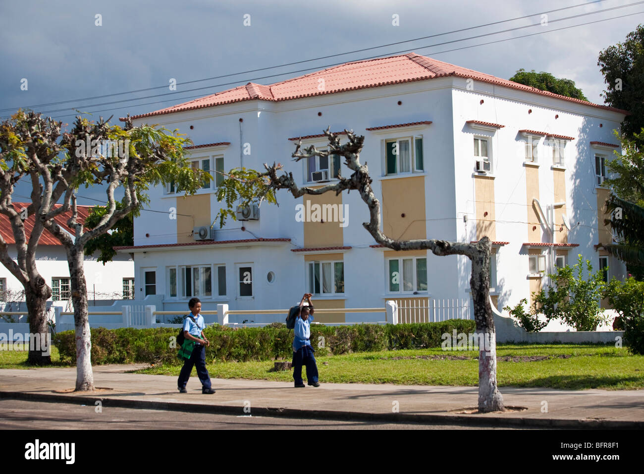 White building with schoolboys walking past - Stock Image