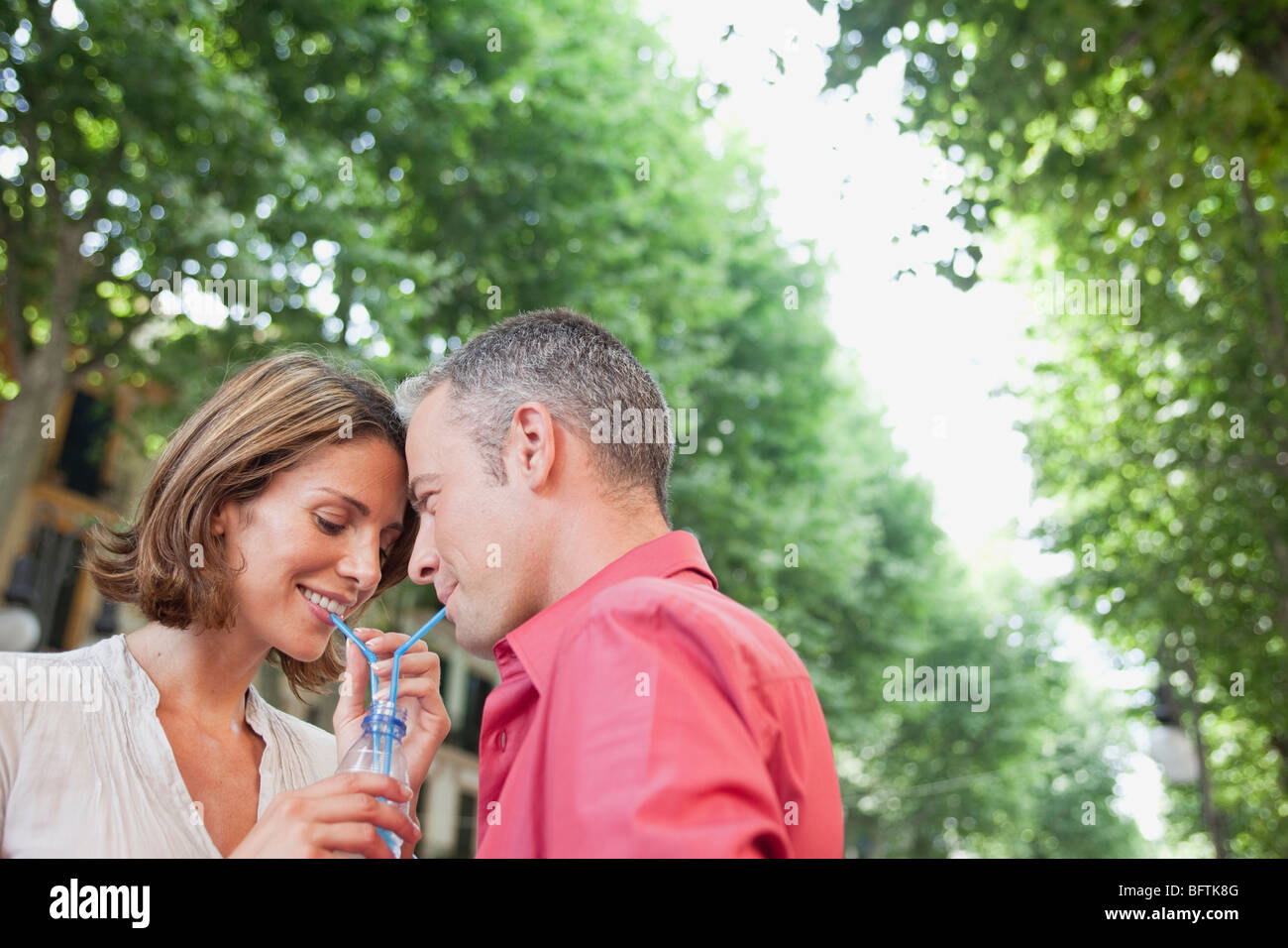 couple drinking out same glass - Stock Image