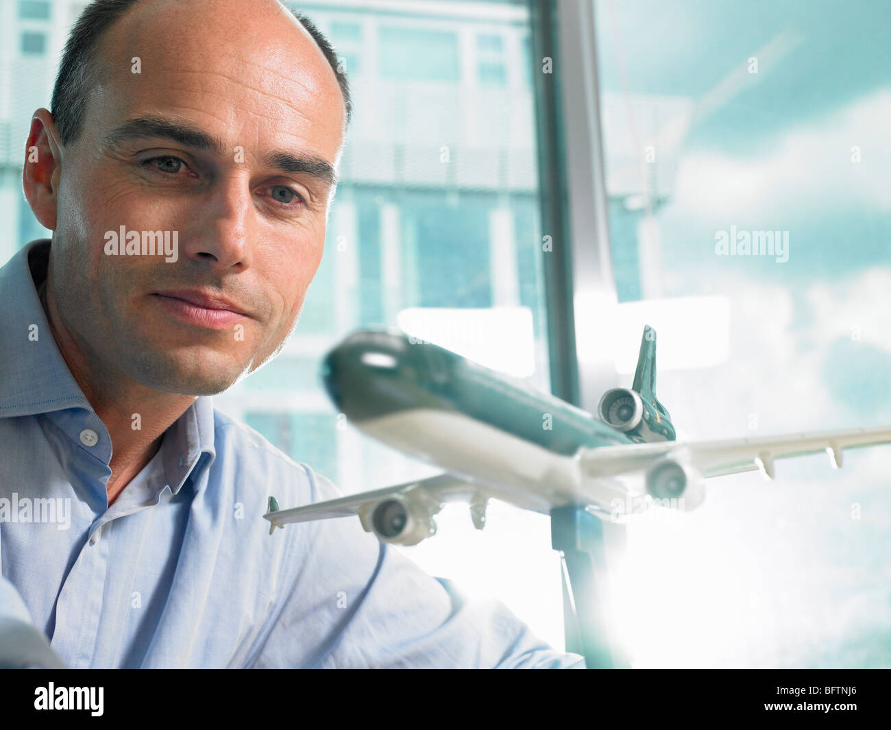 Man looking at a reduced plane model - Stock Image