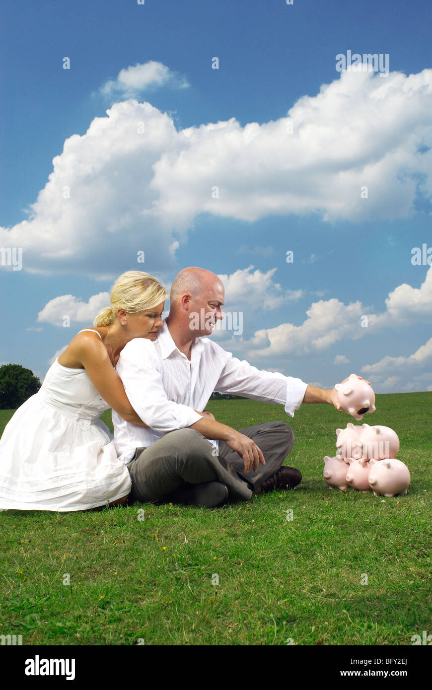couple stacking piggy banks - Stock Image