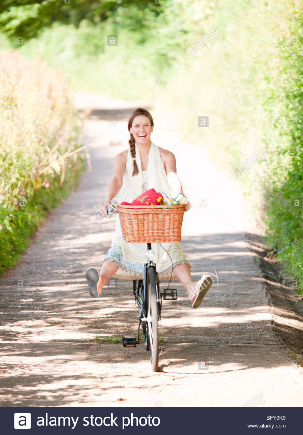 Woman cycling in country lane - Stock Image