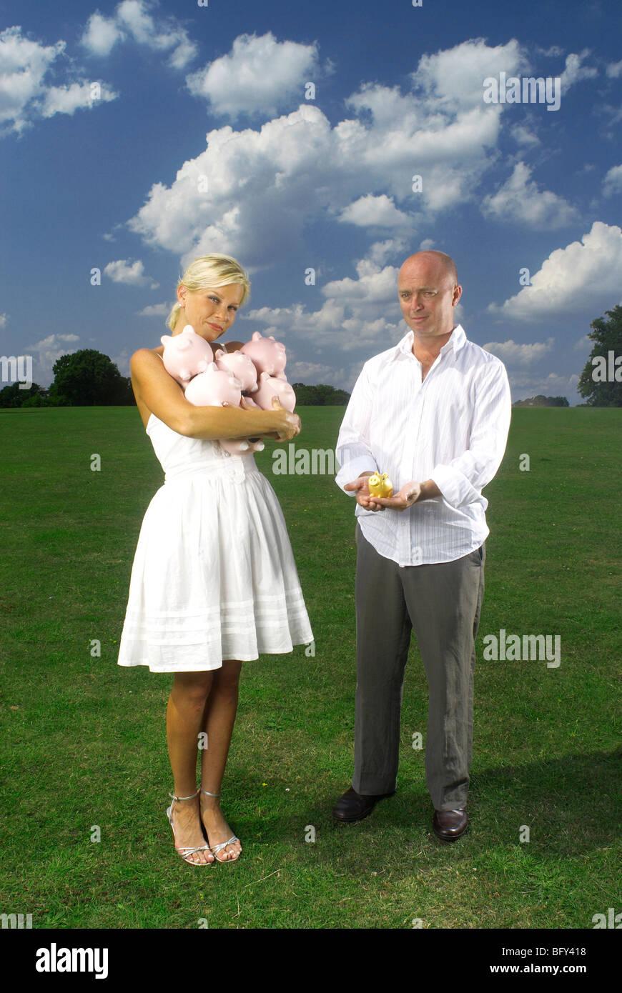 couple holding piggy banks - Stock Image