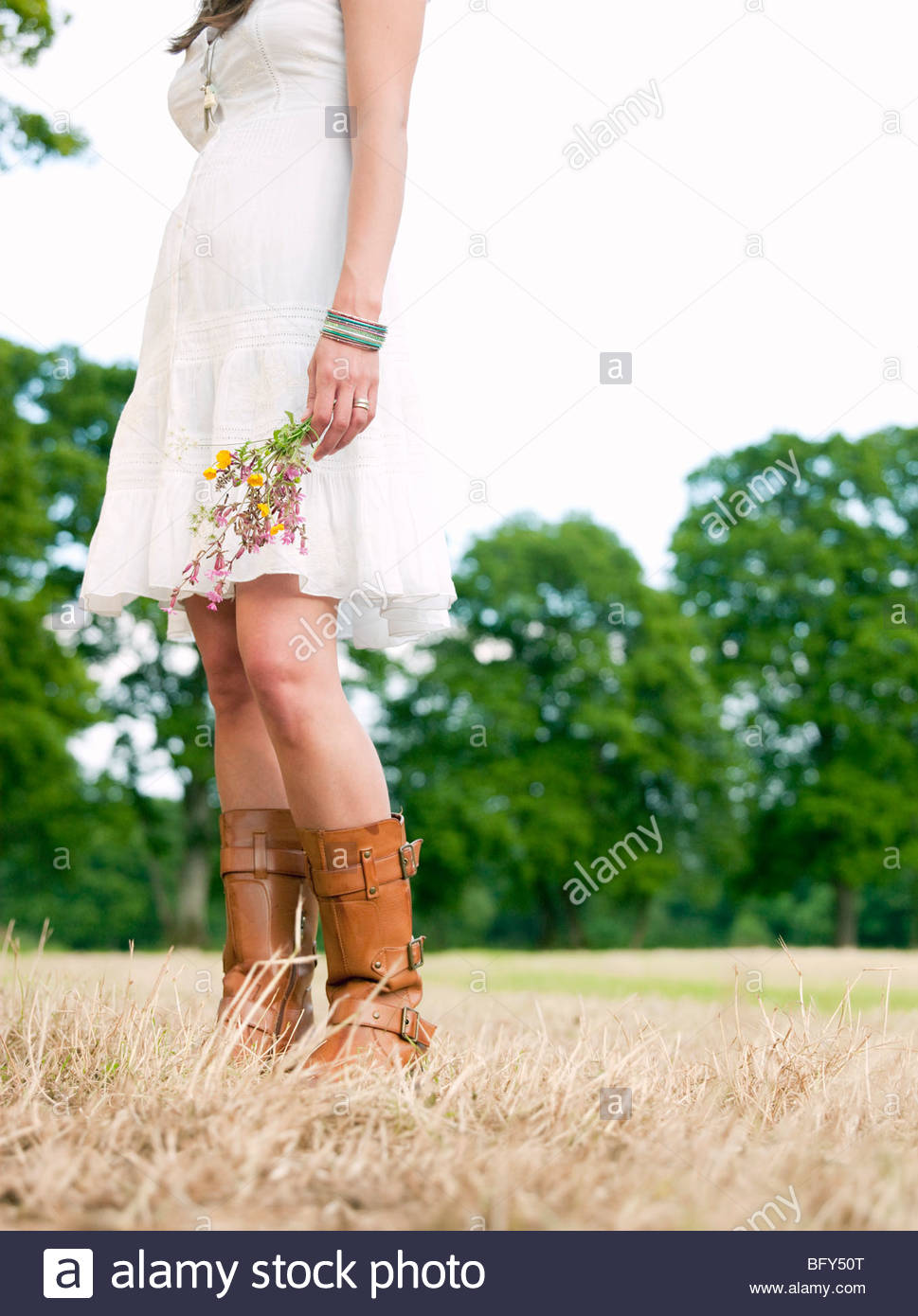 Woman in field holding flowers - Stock Image