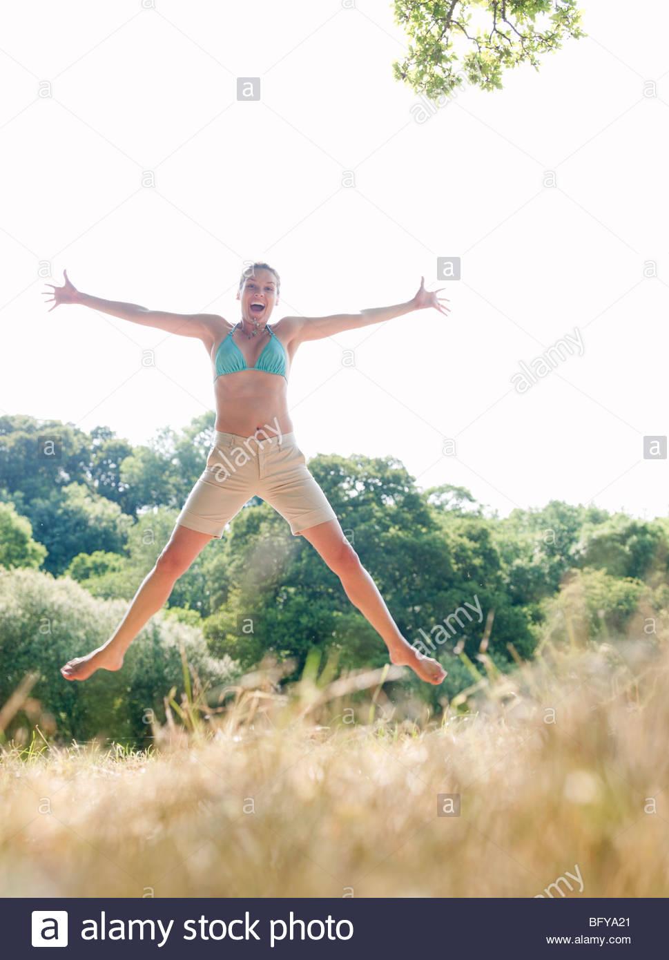 Woman in bikini jumping in country field - Stock Image