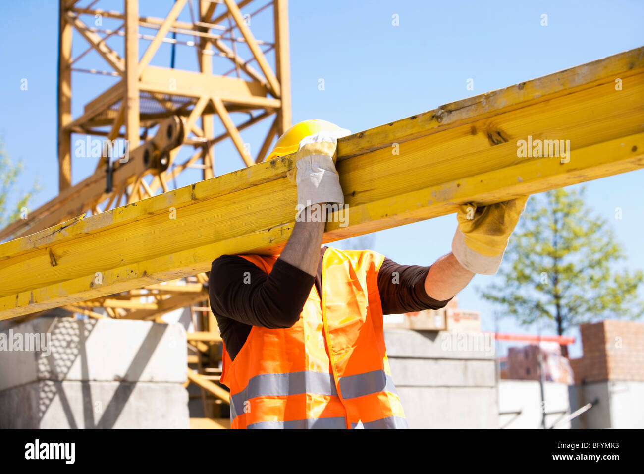 construction worker carrying wooden plank - Stock Image