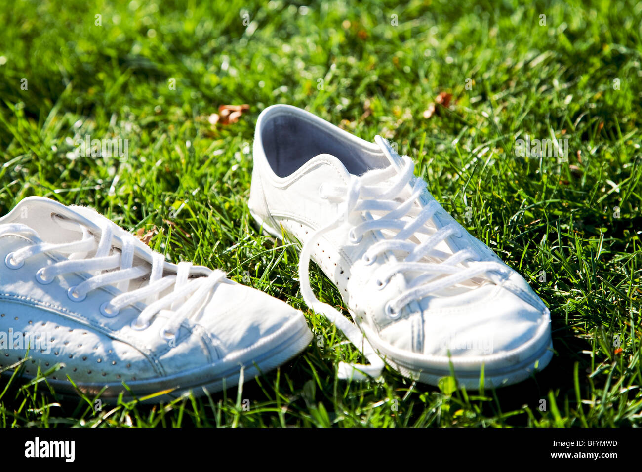 pair of white trainers in grass - Stock Image