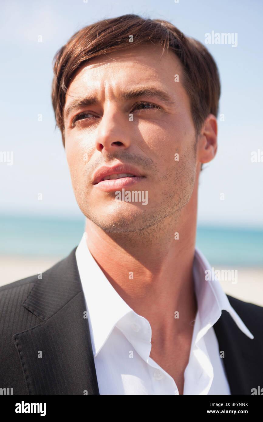 groom on beach looking around - Stock Image