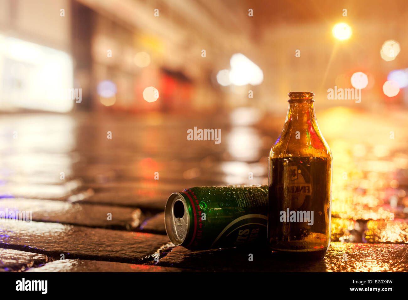 Empty beer containers on wet street - Stock Image