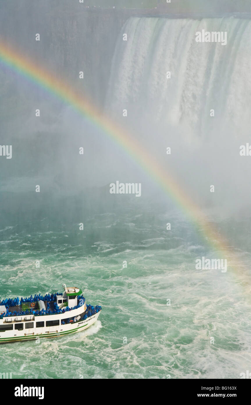 Maid of the Mist tour excursion boat under the Horseshoe Falls waterfall with rainbow at Niagara Falls, Ontario, - Stock Image
