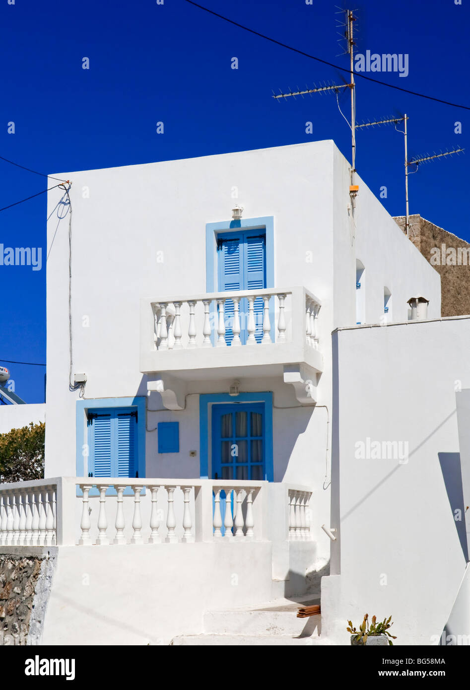 Typical Greek house with white painted walls and blue shuttered windows and doors on the island of Nisyros in the Aegean Sea & Typical Greek house with white painted walls and blue shuttered ...