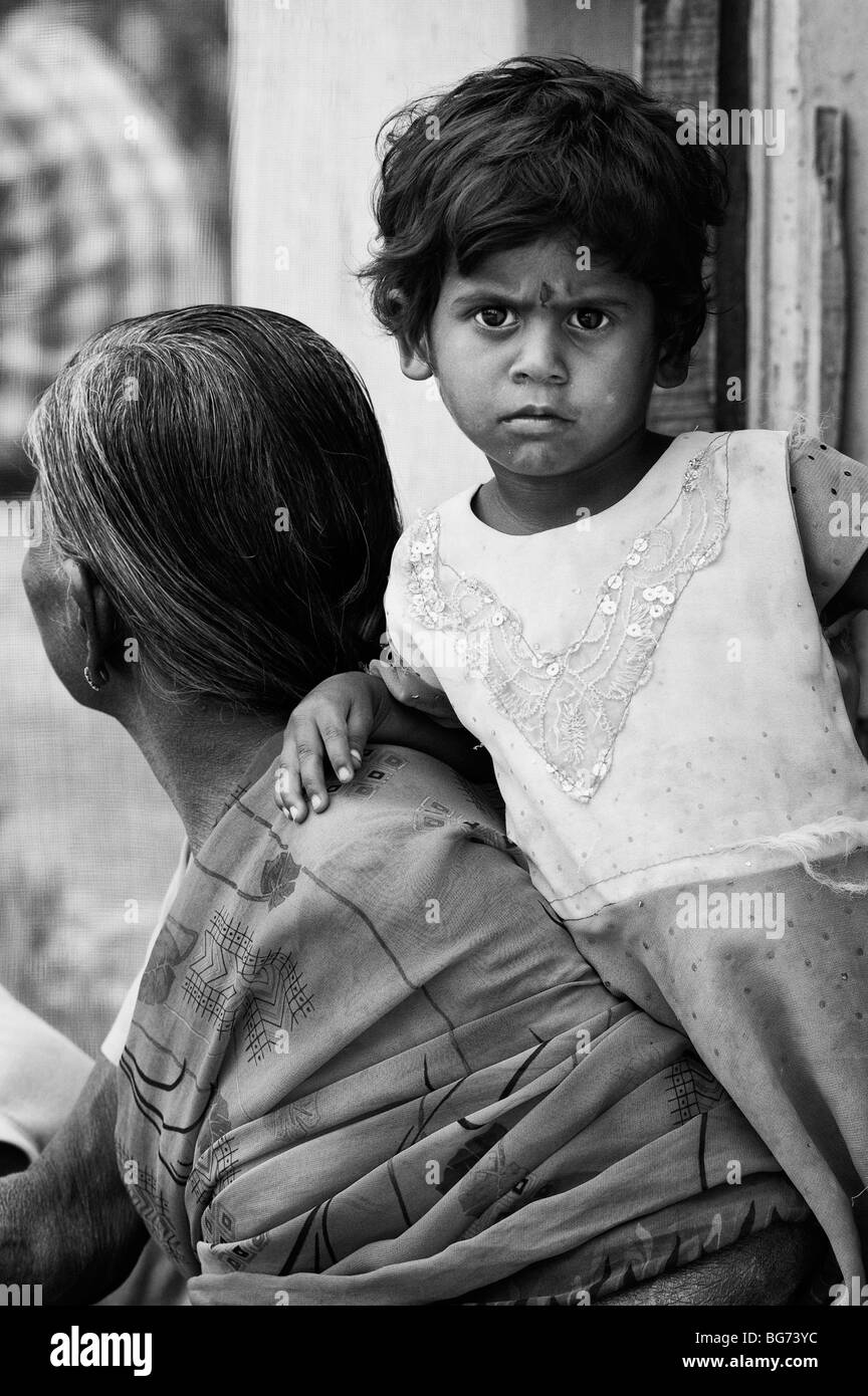 Indian toddler leaning on her grandmother in the doorway of there house in a rural indian village. Andhra Pradesh, - Stock Image