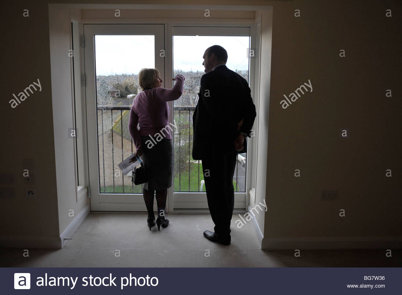 Estate agent showing a prospective buyer around a new build property. - Stock Image