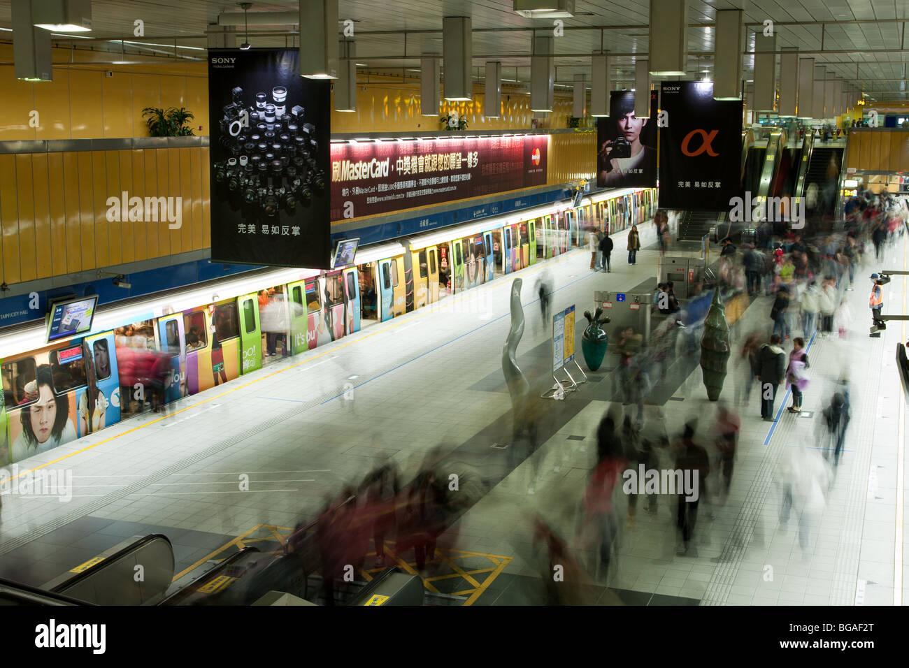 People wait, walk underground on the platform of Taipei City Hall Metro Station in Taipei, Taiwan. Blurring moving Stock Photo