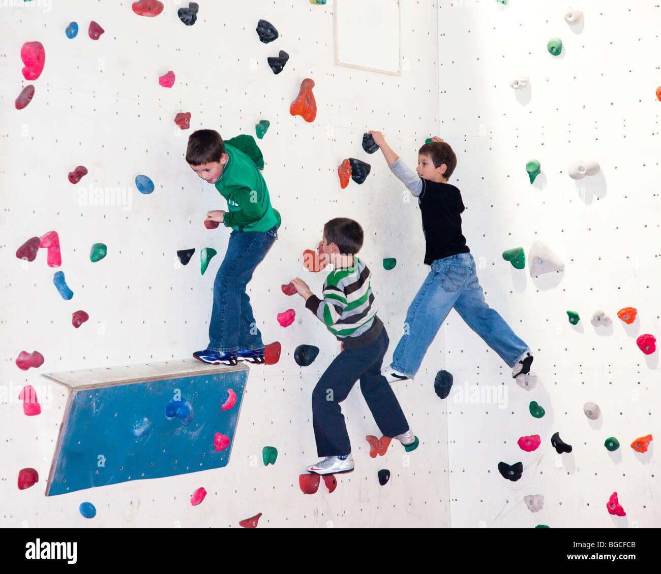 Children practice climbing on indoor climbing wall Cardiff Wales UK - Stock Image