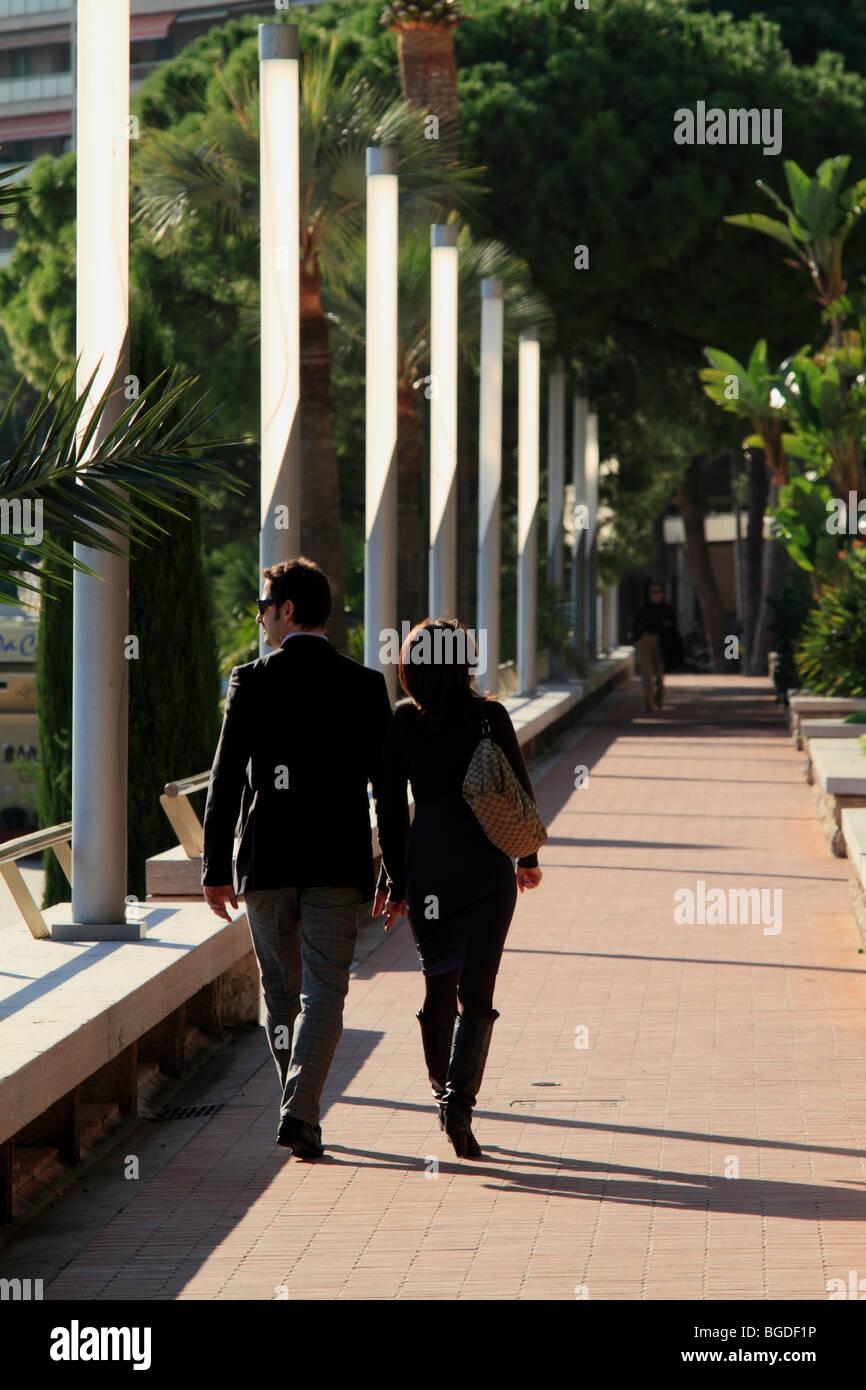 Wealthy couple on the beach promenade of Larvotto, Principality of Monaco, Cote d'Azur, Europe - Stock Image