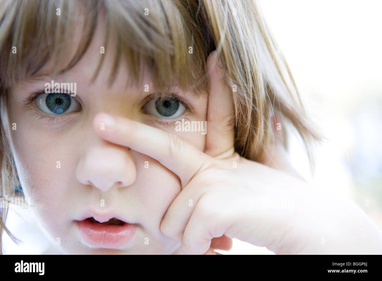 eight year old child looking at camera with fingers on her faceStock Photo