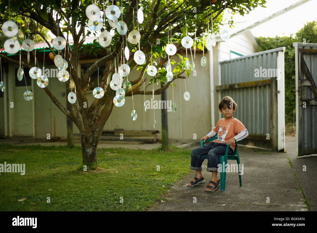 Boy sits beneath fruit tree with discs hanging from its branches - Stock Image