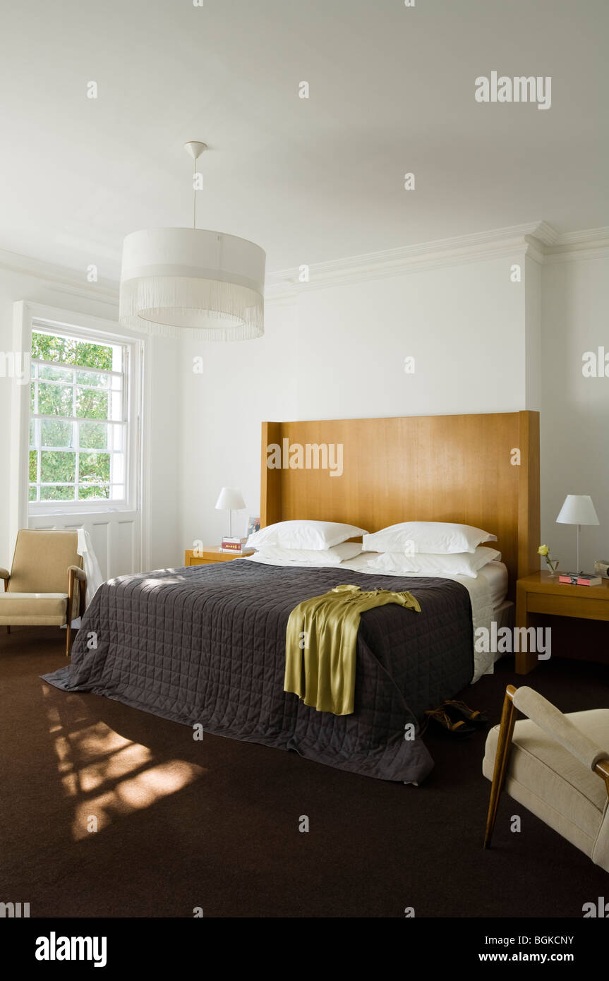 Double bedroom with black quilt and white lightshade - Stock Image