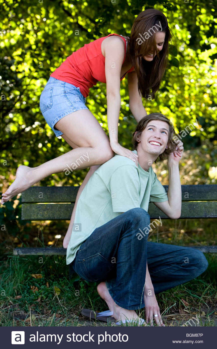 A young couple having fun on a park bench - Stock Image