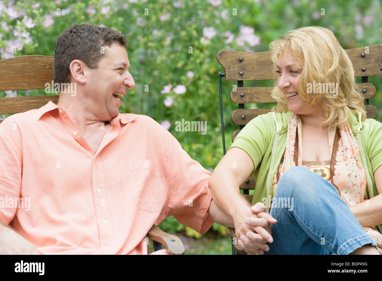 Couple Mature mature couple sitting on chairs and holding each other's hands stock