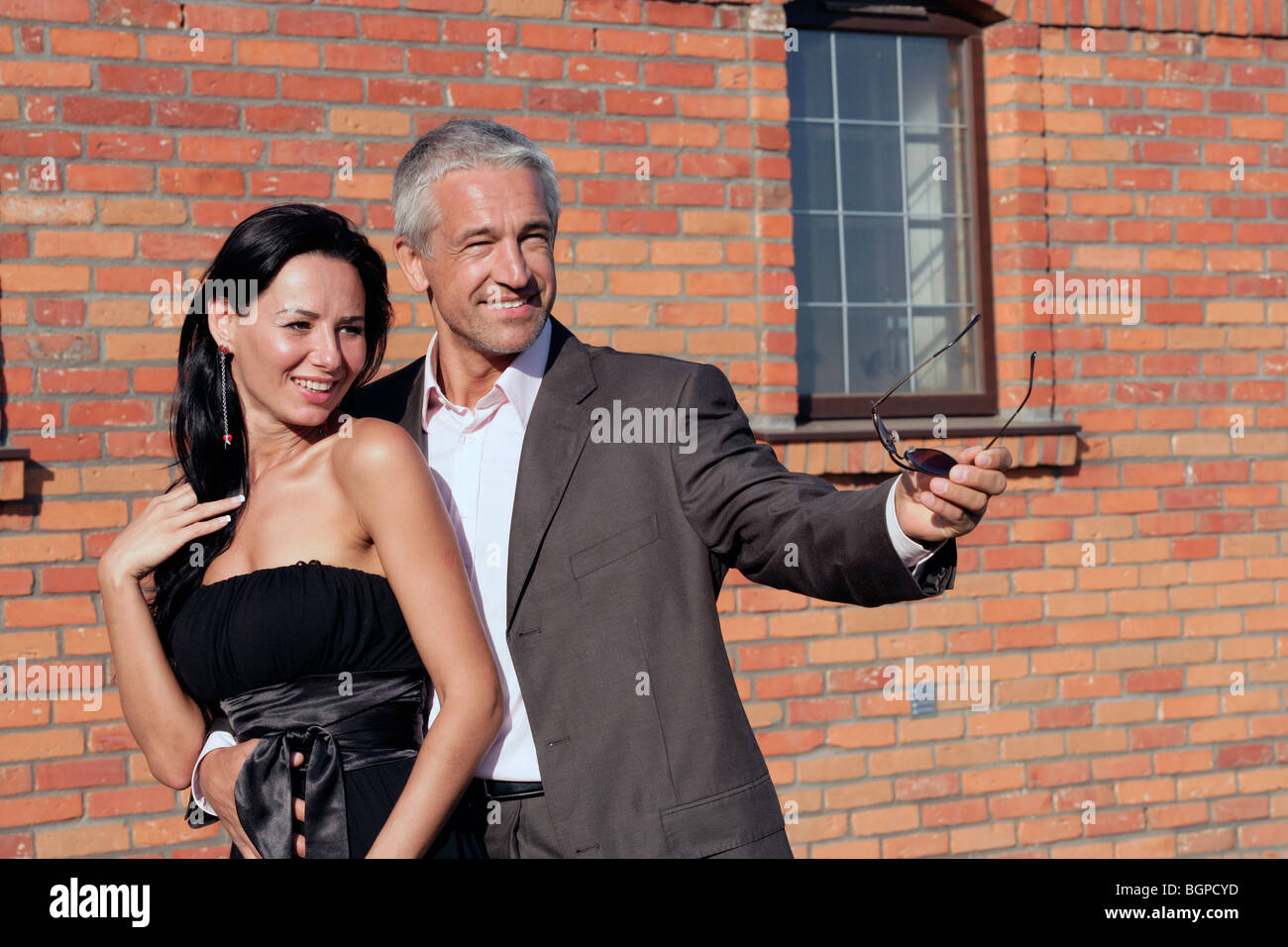 Attractive happy couple standing next to brick wall - Stock Image