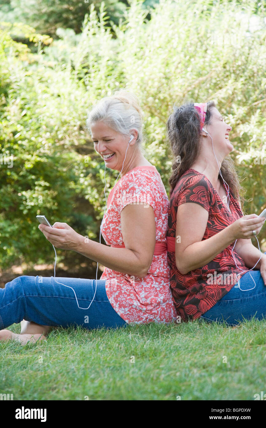 Side profile of two mature women sitting back to back in a park and listening to MP3 players - Stock Image