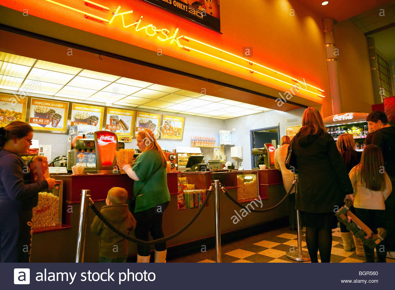 Cinema kiosk selling popcorn, coca cola and hot drinks, Gloucester, UK. People queuing at shop inside cinema. High Stock Photo