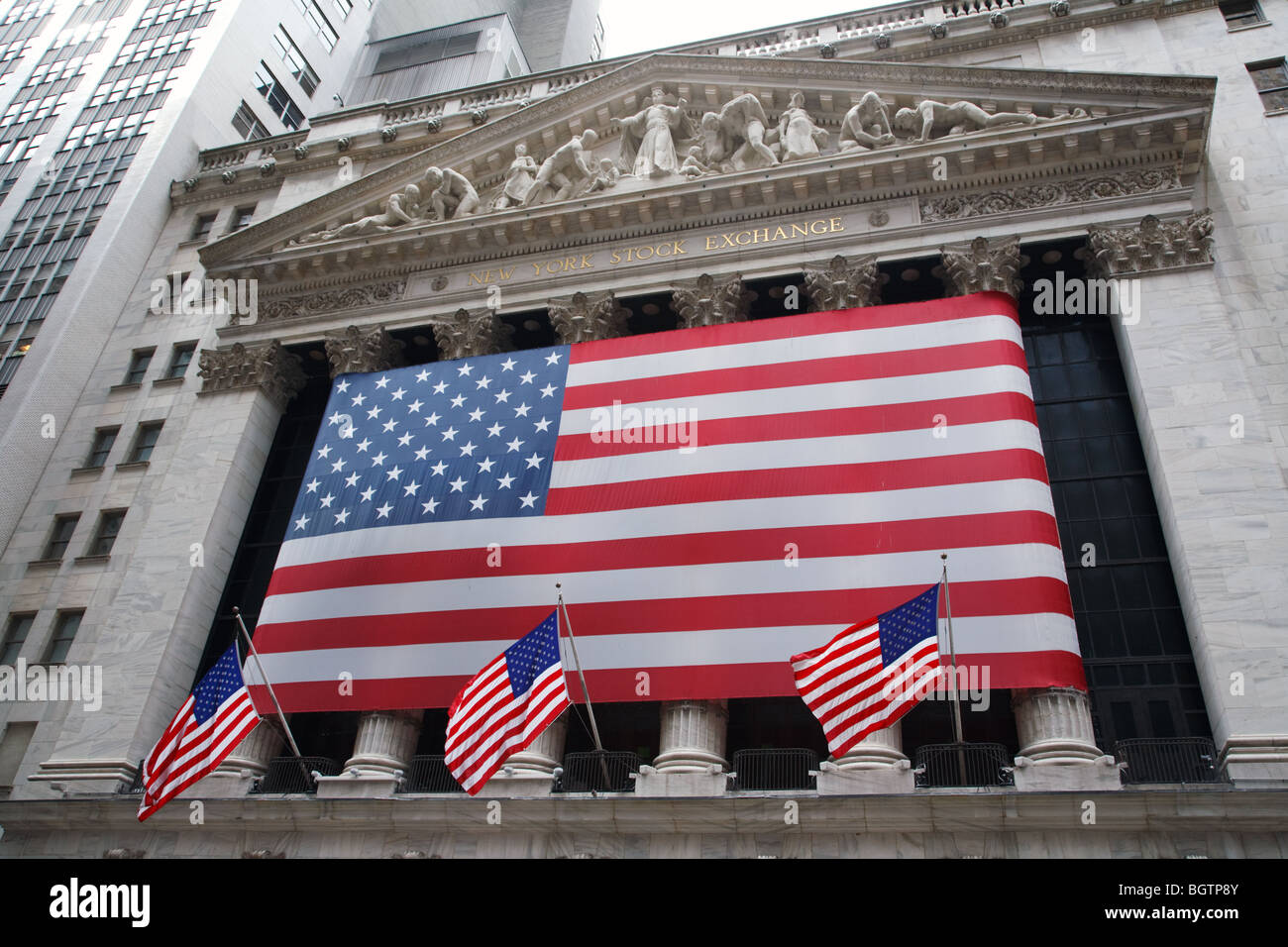 The American flag on the side of New York Exchange building in Wall Street, New York City, USA - Stock Image