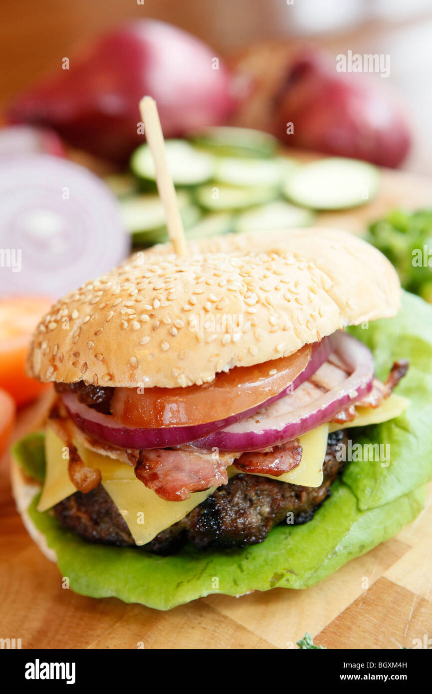 Burger being prepared, with cheese, bacon and garnish in a restaurant - Stock Image