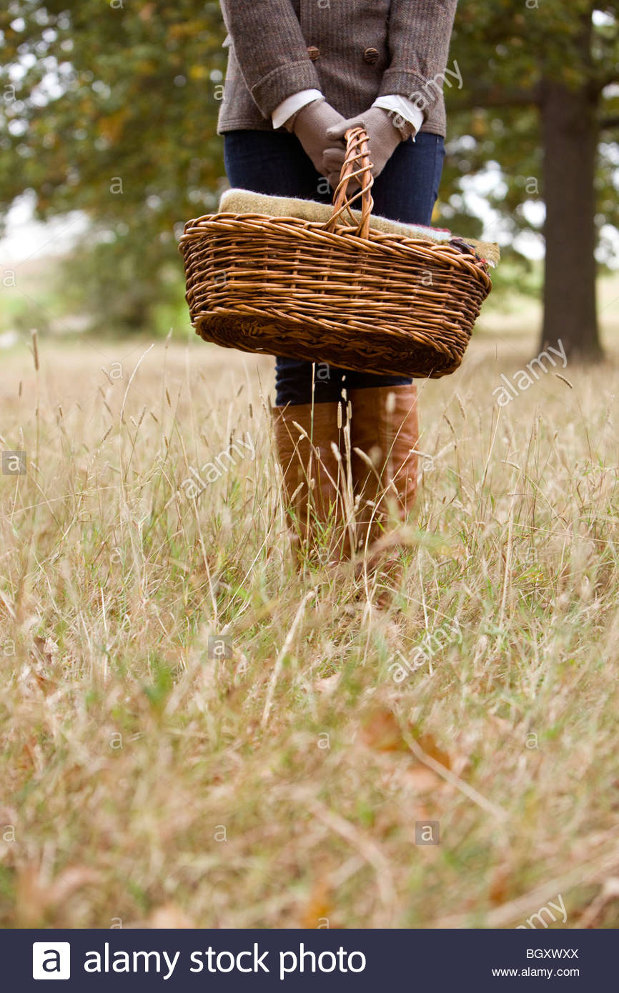 A young woman standing in a field, holding a wicker basket - Stock Image