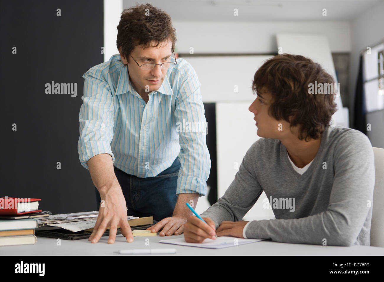 Teacher assisting college student - Stock Image
