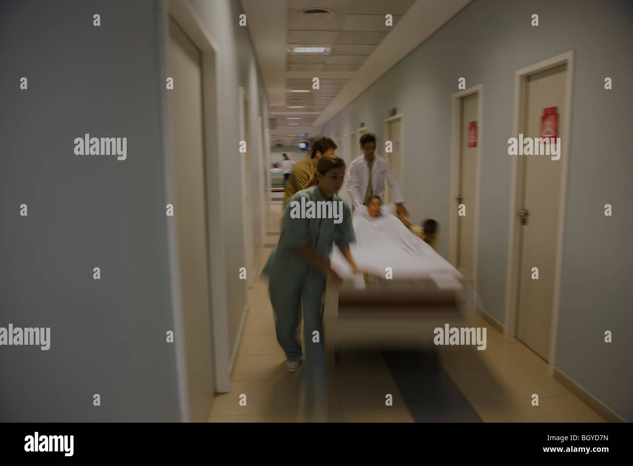 Healthcare workers running with patient on gurney in hospital corridor - Stock Image