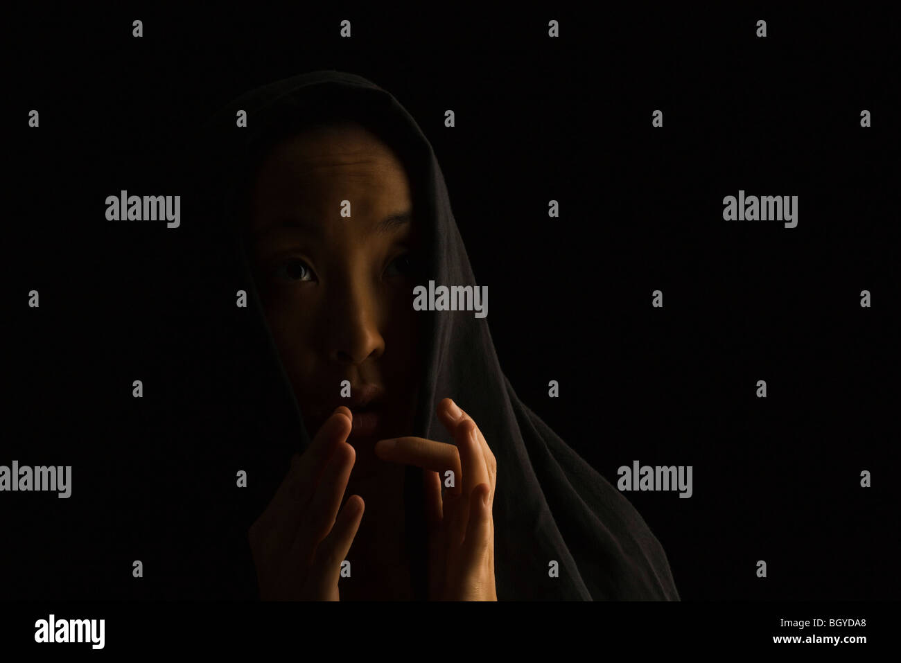 Woman wearing headscarf, hands fearfully held up before face, looking up - Stock Image
