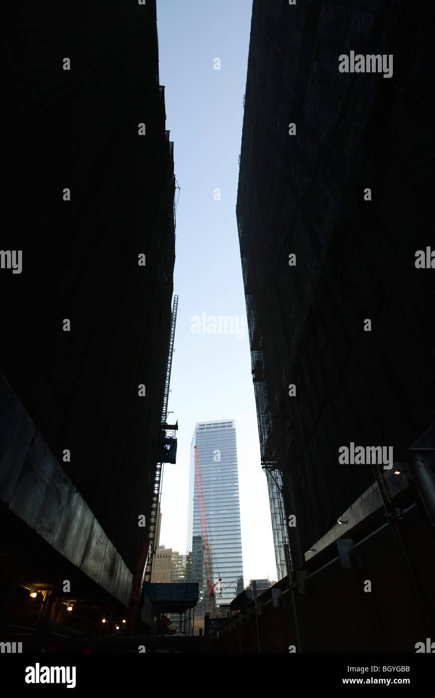 Buildings under construction, skyscraper in background - Stock Image