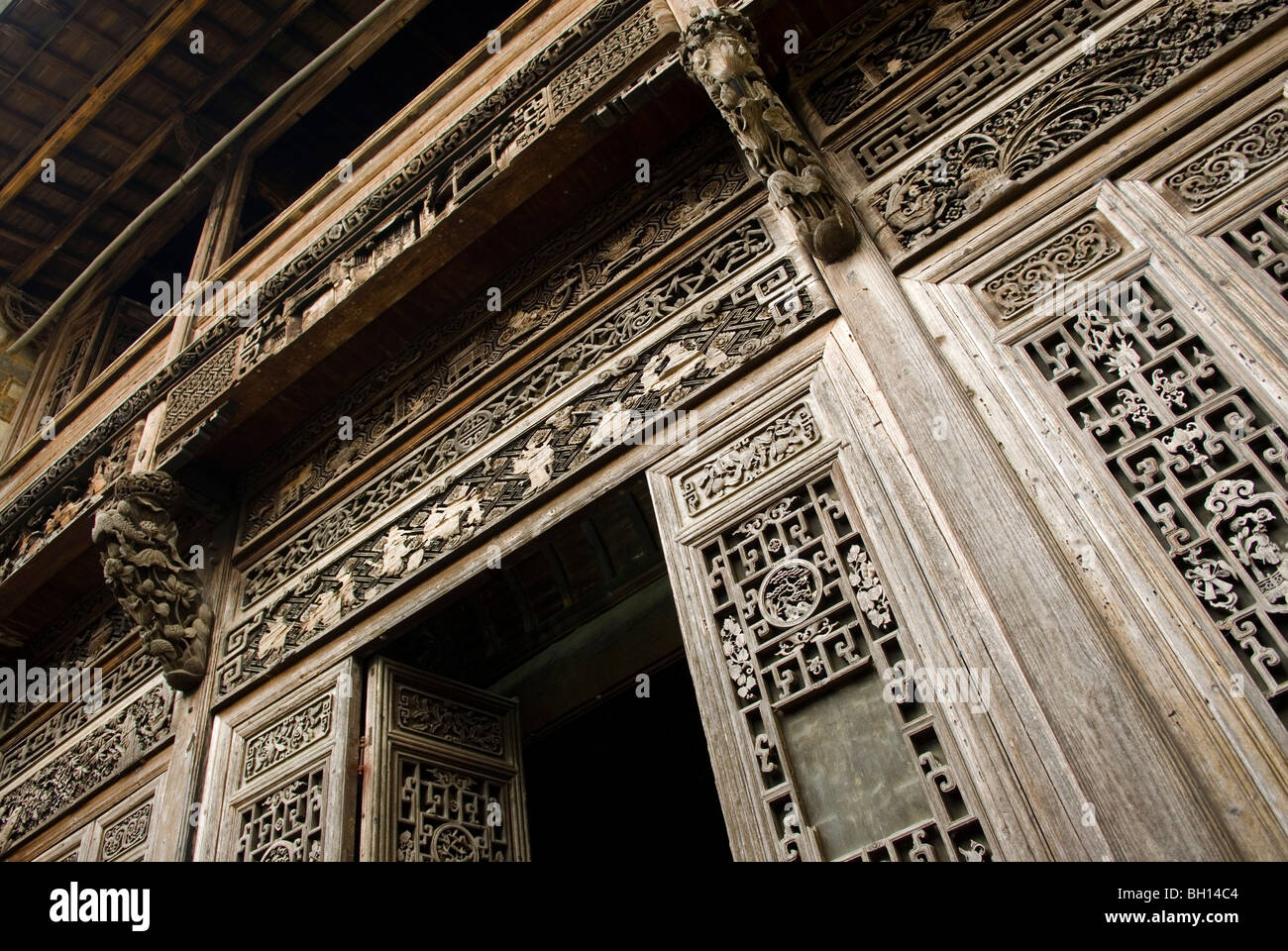 Elaborately wood carved doors and panels in ancient wealthy merchant's dwelling. Sixi. Jiangxi, China. - Stock Image