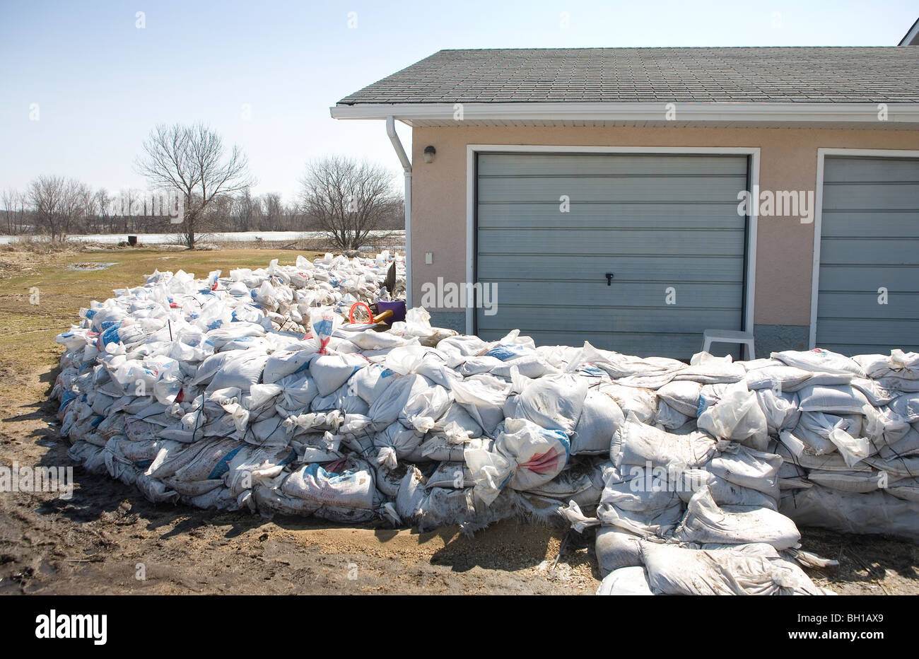 Dyke of sandbags around rural home to protect from Red River floodwaters, Manitoba, Canada - Stock Image