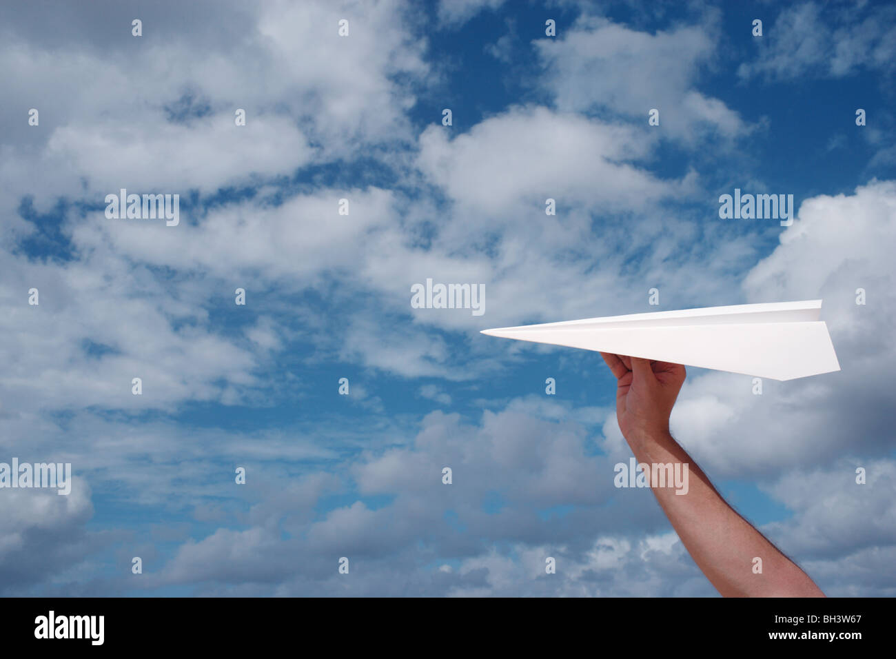 A man's hand holding a white paper airplane in a blue cloudy sky - Stock Image