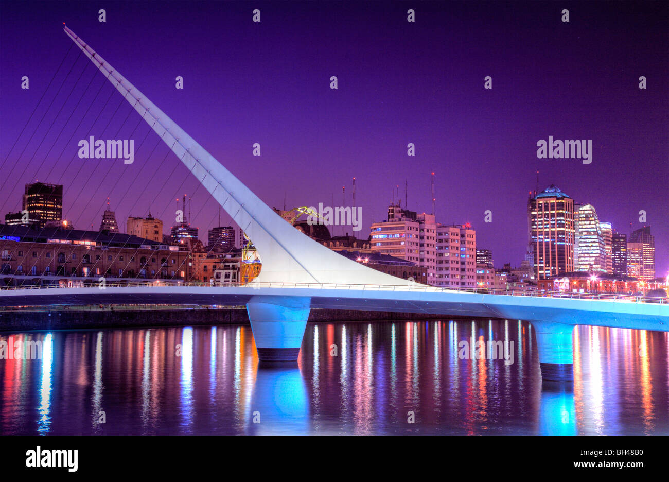 Bridge of the Woman view at dusk, with city silhouette at background and water reflections. Puerto Madero, Buenos - Stock Image