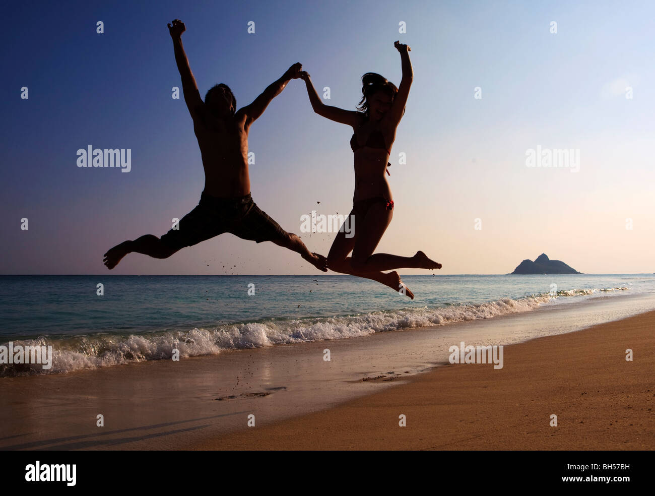 silhouette of couple jumping in the air at a hawaii beach - Stock Image