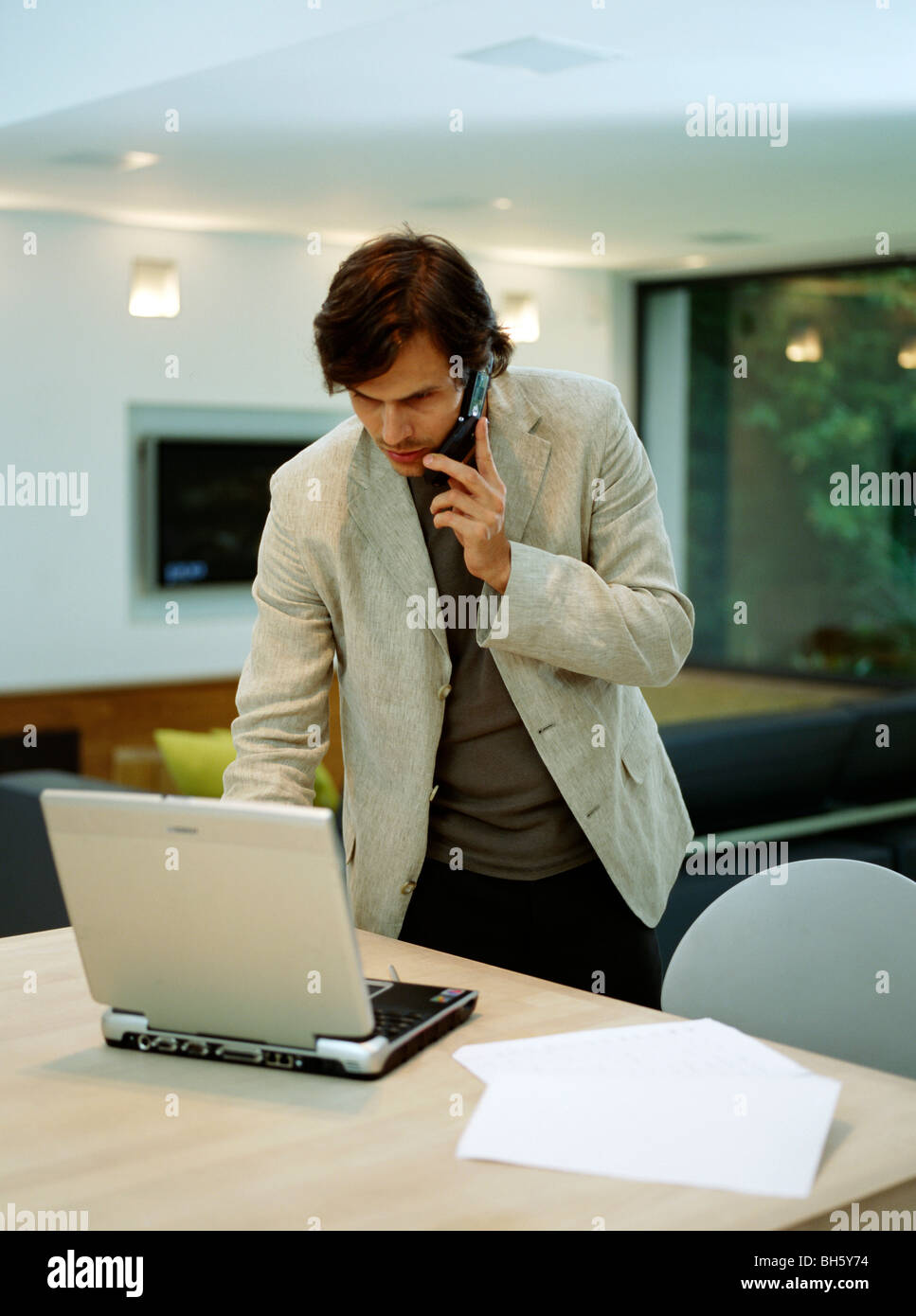 A young trendy male works from home - Stock Image