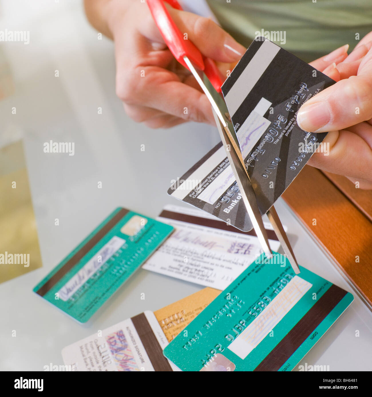 Woman cutting credit cards - Stock Image