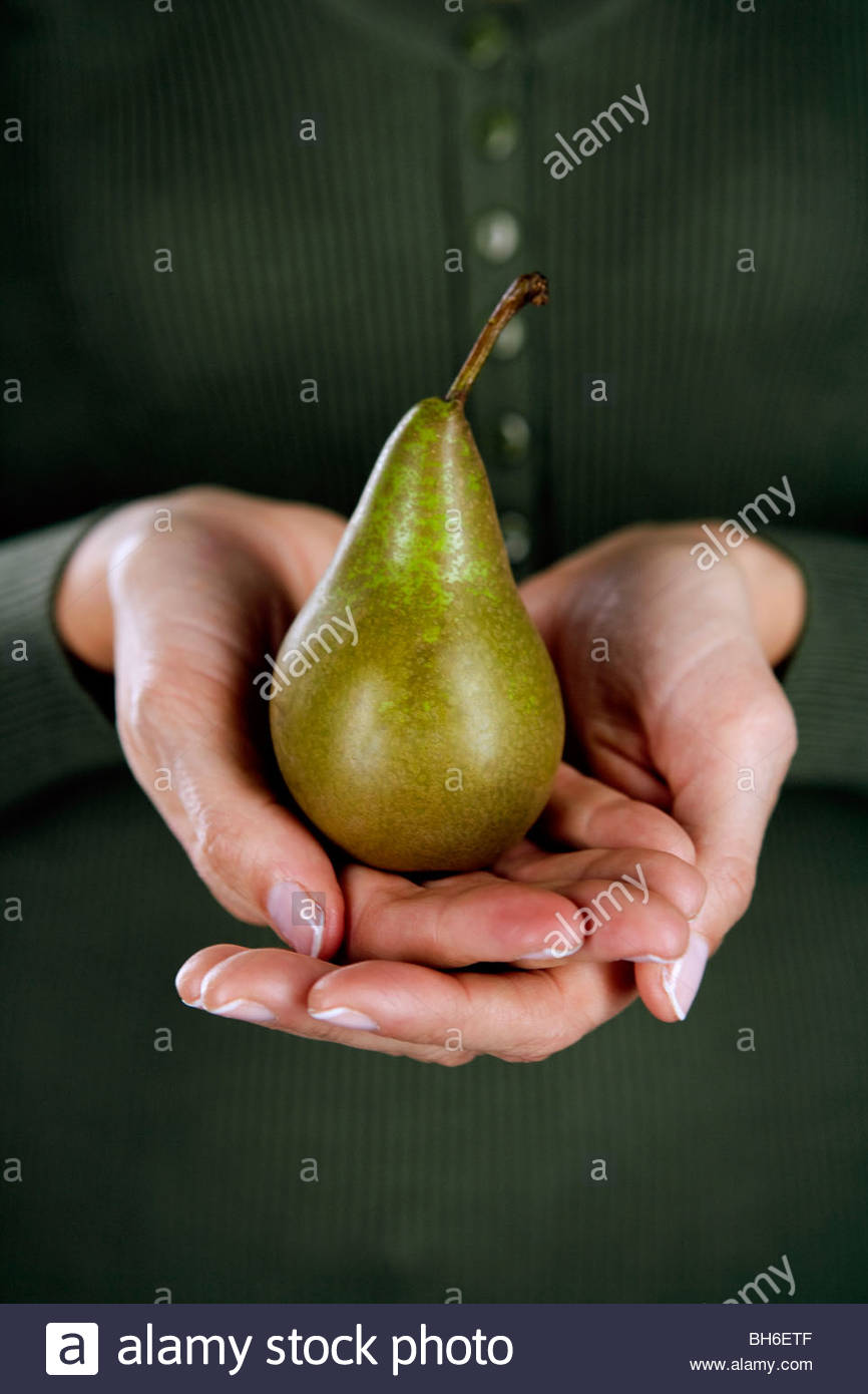A woman holding a pear in her hands - Stock Image