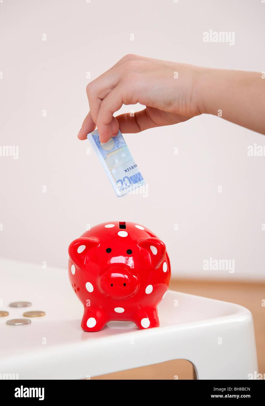 saving money in piggy bank - Stock Image
