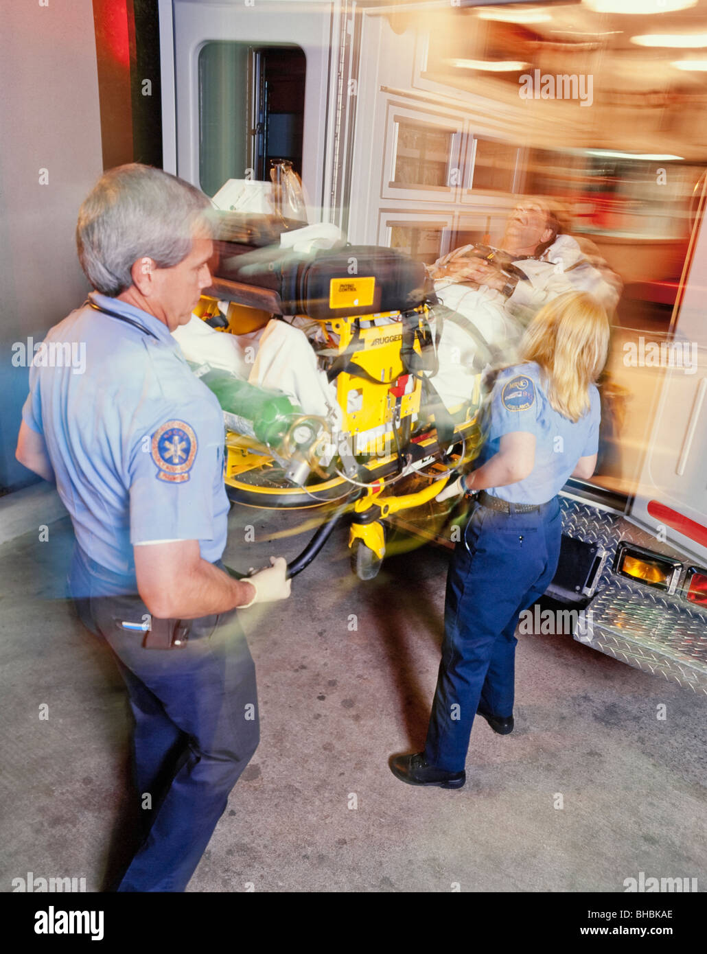 Emergency medical technicians loading patient into ambulance - Stock Image